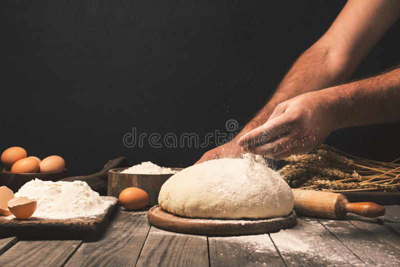 Les mains d'hommes arrosent la fin de farine de la pâte  photos libres de droits