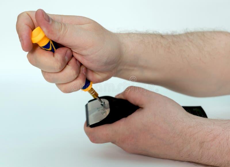 Les mains d'hommes d?tordent les boulons avec une tondeuse de lame de tournevis les cheveux photo stock