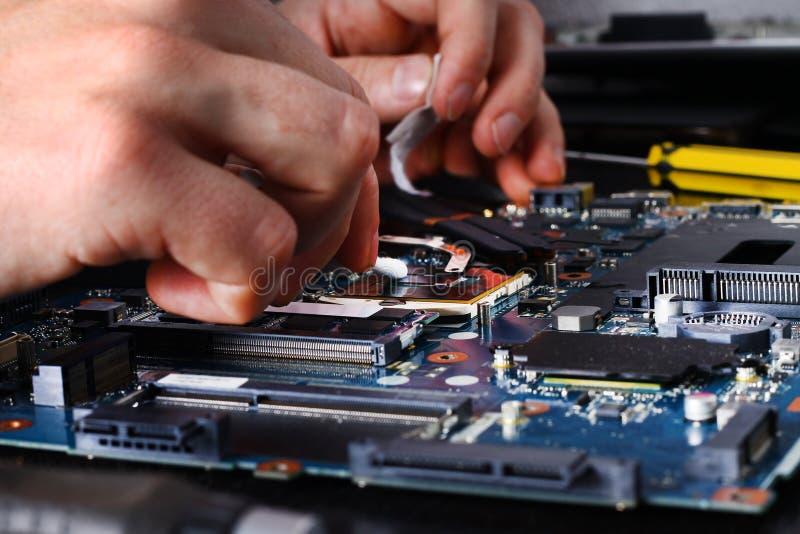 Les mains d'hommes de réparation de culture informatique, homme examine la pâte thermique propre d'ordinateur portable photographie stock