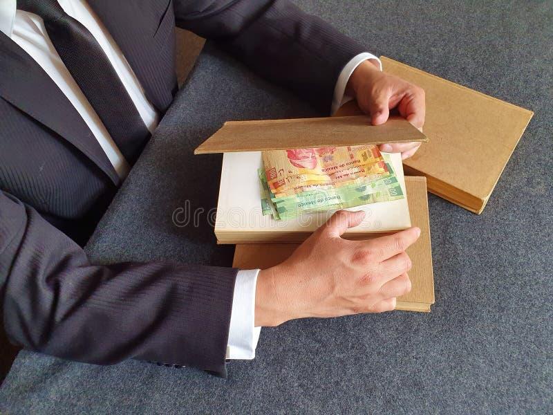 les mains d' un homme d' affaires avec de l' argent mexicain et des livres sur la table photos stock
