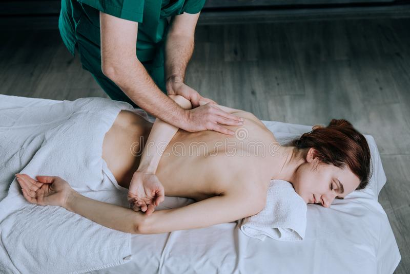 Les mains d'un masseur masculin faisant le massage d'une jeune femme Beau visage décontracté d'une jeune femme 27 années avec le  photo stock
