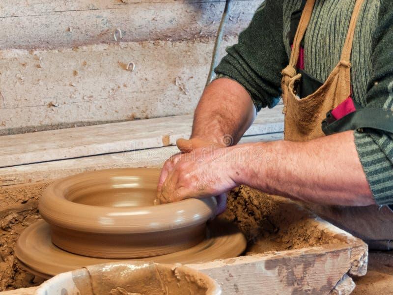 Les mains d'un potier font un grand pot images stock