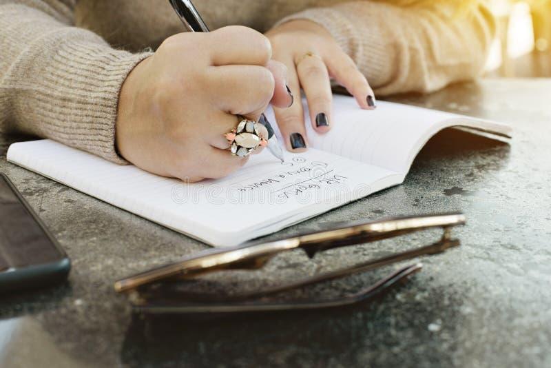Les mains d'une femelle notent ses buts de la vie dans un journal image libre de droits