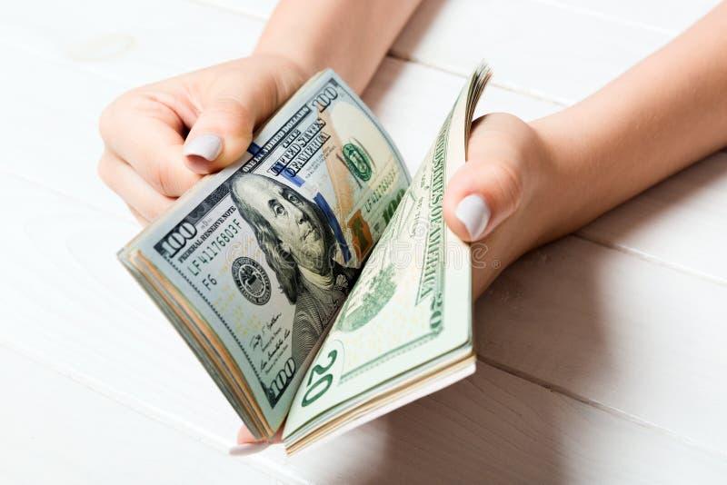 Les mains d'une femme d'affaires comptant 100 dollars de factures sur fond de bois. Concept de salaire et de salaire. Perspective images libres de droits