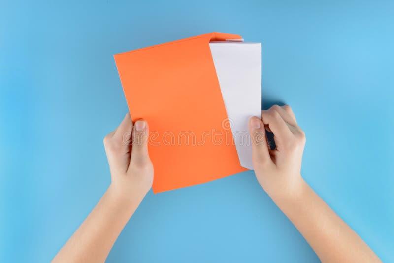 Les mains d'une jeune fille sortent une feuille blanche d'une enveloppe orange Photo sur un fond bleu L'espace pour le texte, rai photographie stock