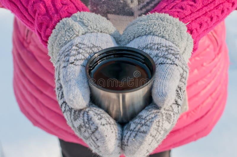 Les mains dans des mitaines tiennent une tasse d'un thermos avec le thé image stock