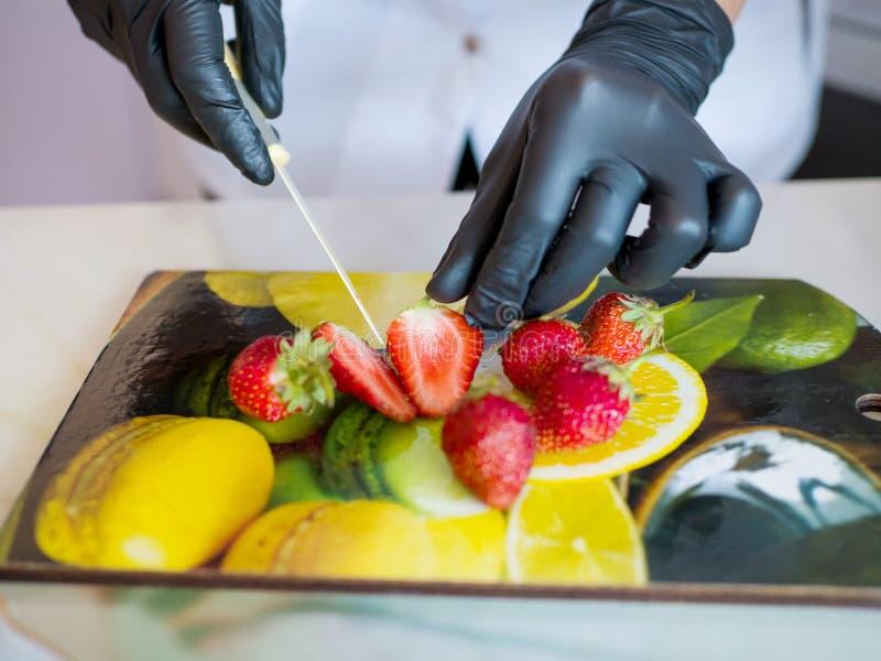 Les mains dans les gants en caoutchouc noirs ont coupé une fraise rouge mûre sur un tableau noir photos libres de droits