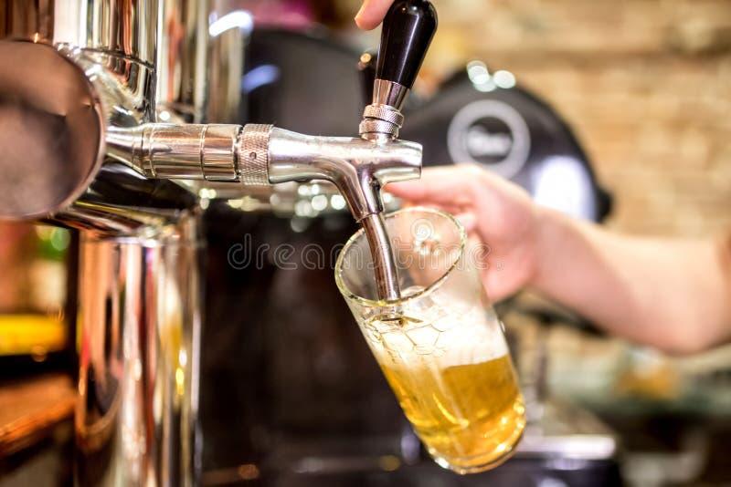 les mains de barman à la bière tapent verser une portion de bière blonde d'ébauche dans un restaurant ou un bar photos stock