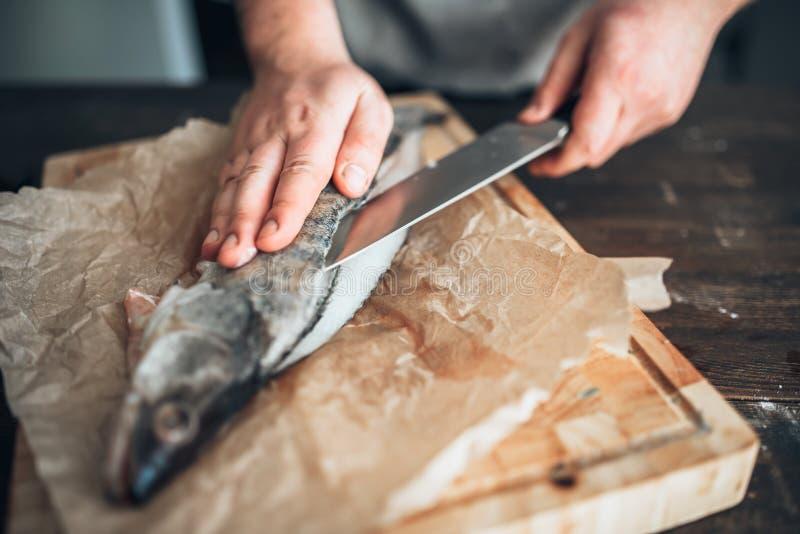 Les mains de chef avec le couteau ont coupé des poissons sur la planche à découper images stock