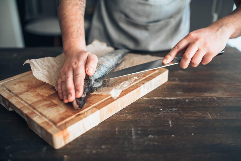 Les mains de chef avec le couteau ont coupé des poissons sur la planche à découper photo stock