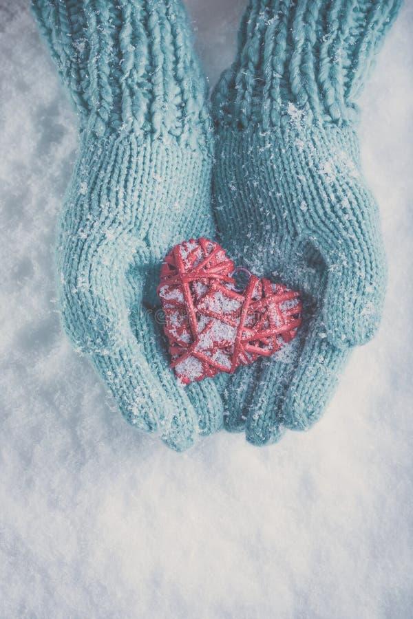 Les mains de femme dans des mitaines tricotées par sarcelle d'hiver légère tiennent le beau coeur rouge brillant sur le fond de n images stock