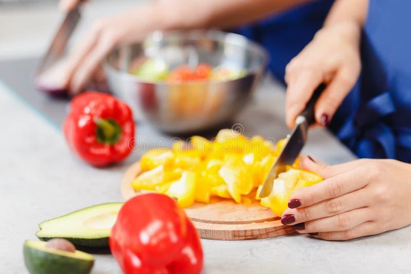 Les mains de femme ont coupé le poivre jaune pour la salade végétale Atelier de nourriture de concept image stock