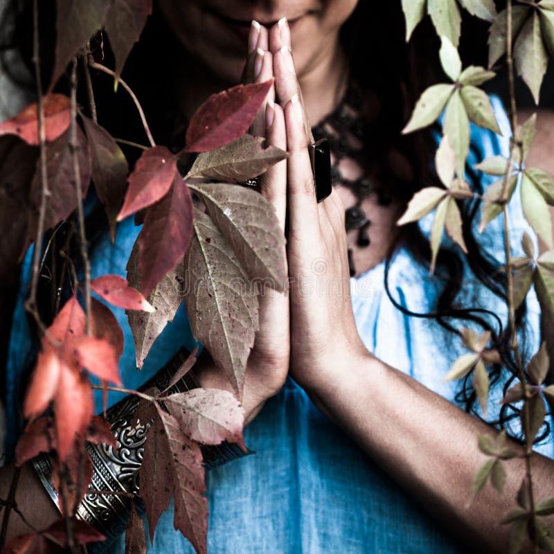 Les mains de femme de plan rapproché dans le namaste font des gestes le tir extérieur photos stock
