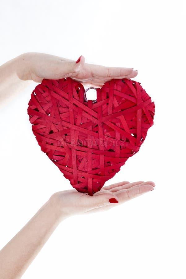 Les mains de femme tiennent le coeur en osier rouge photo libre de droits