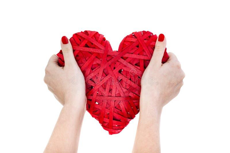 Les mains de femme tiennent le coeur en osier rouge photos libres de droits