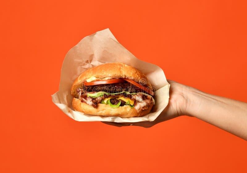 Les mains de femme tiennent le grand sandwich à barbecue de cheeseburger avec du boeuf de marbre image libre de droits