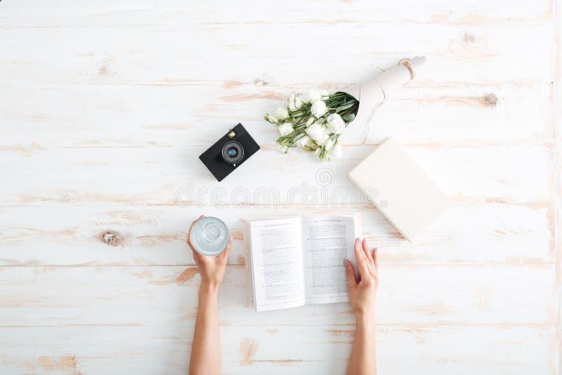 les mains de femmes ouvrent le livre sur le bureau en bois photo stock image du fleurs revue. Black Bedroom Furniture Sets. Home Design Ideas