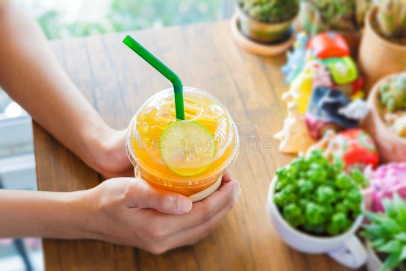 Les mains de femmes tiennent le citron de thé de glace sur la table et le cactus en bois près de l'herbe de fenêtre photos libres de droits