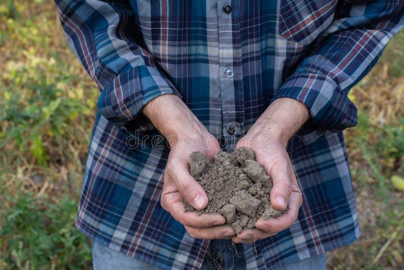 Les mains de ferme avec un sol fertile photo stock