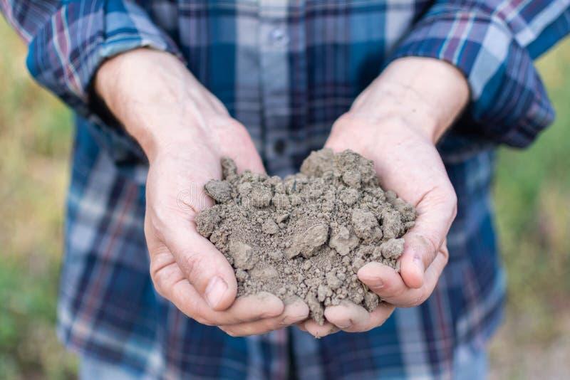 Les mains de ferme avec un sol fertile image stock
