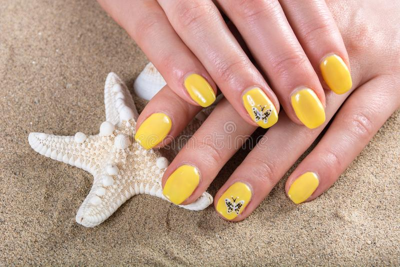 Les mains de fille avec jaunes vernis à ongles sur le sable et les étoiles de mer de plage de mer photos stock