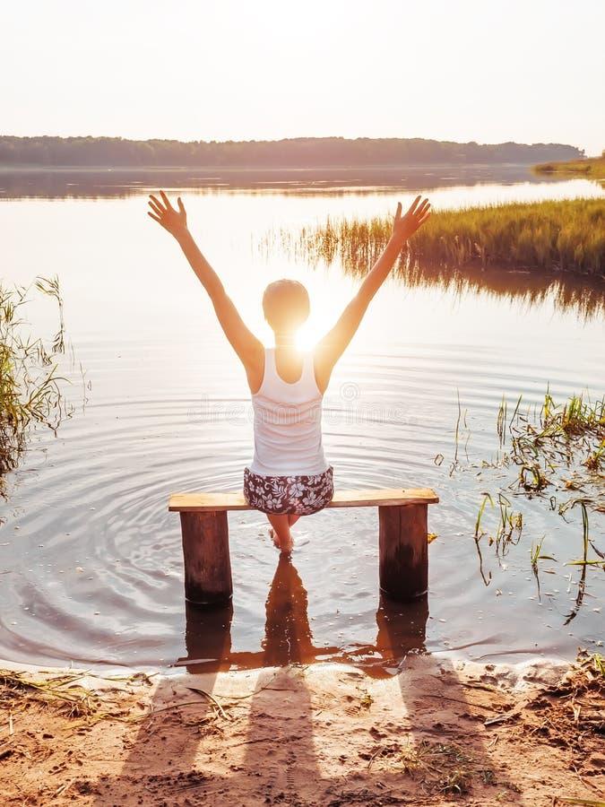 les mains de fille s'ouvrent Les bras de femme ont augmenté  La fille s'assied sur un banc par la rivière et apprécie un beau cou photo stock