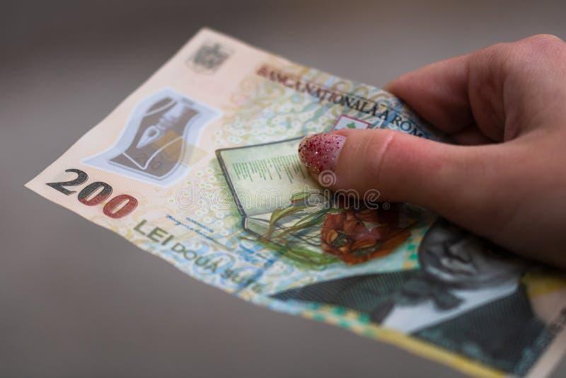 Les mains de filles donnant de l'argent Détention de billets LEI sur fond flou, monnaie roumaine photos stock