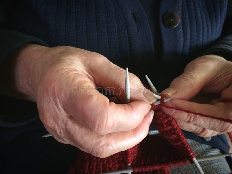 Les mains de grand-mère tricotent le fil de laine rouge Dame supérieure, mamie dans le chandail tricoté bleu fait main modèle d'a photo libre de droits