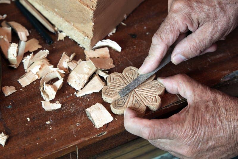 Les mains de l'ébéniste utilisant la râpe sur un morceau de bois photo stock