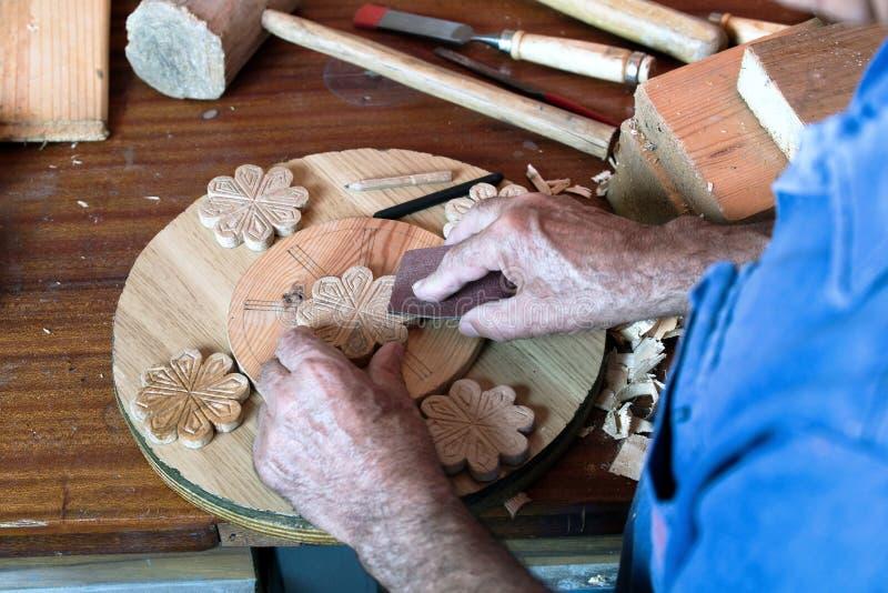 Les mains de l'ébéniste utilisant le papier sablé sur un morceau de bois photographie stock
