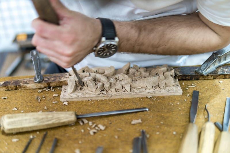 Les mains de l'artisan découpent avec une gouge photos libres de droits