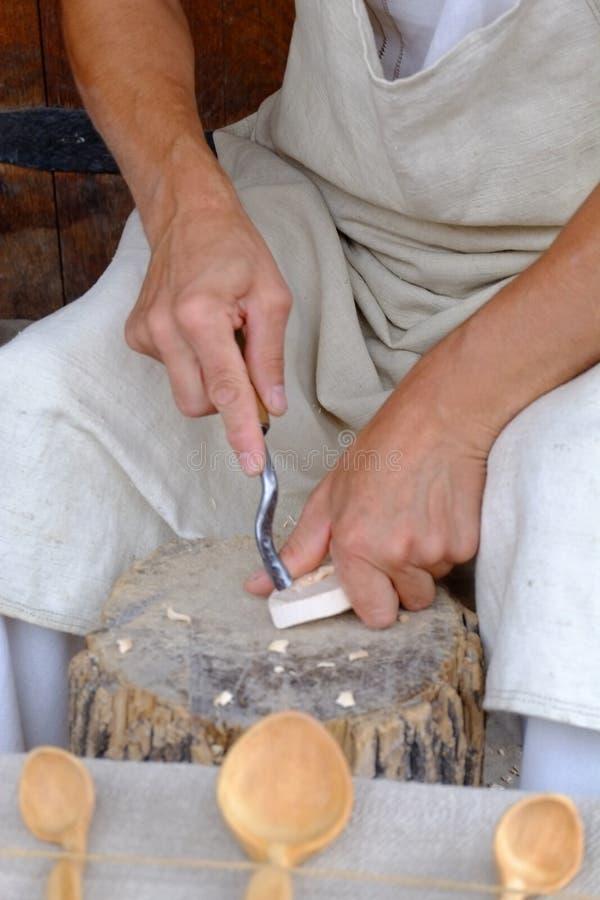 Les mains de l'artisan découpent la gouge en bois de cuillère image stock