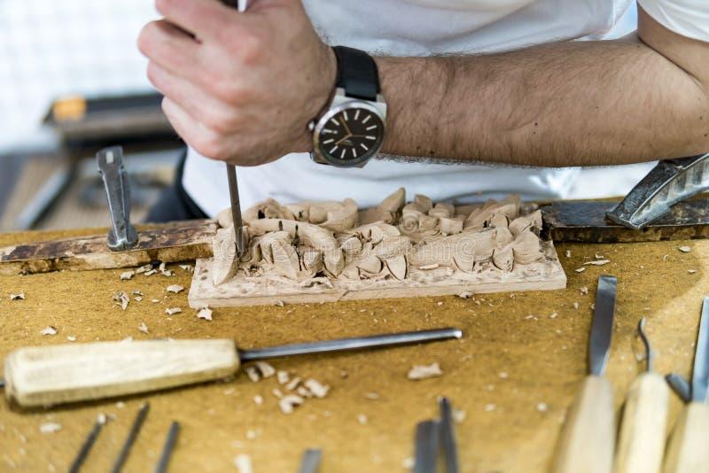 Les mains de l'artisan découpent un bas-relief avec une gouge photos stock