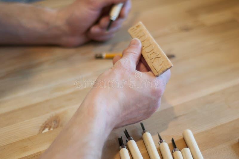 Les mains de l'artisan d?coupent avec une gouge D?coupage du bois Ensemble de découpage en bois sur une table en bois photographie stock libre de droits