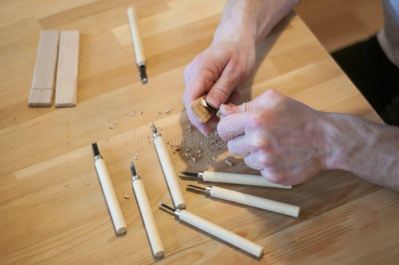 Les mains de l'artisan d?coupent avec une gouge D?coupage du bois Ensemble de découpage en bois sur une table en bois image stock