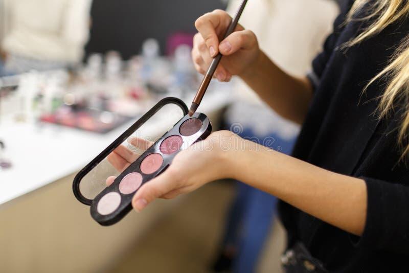 Les mains de l'artiste de maquillage tiennent une brosse et un fard à paupières image libre de droits