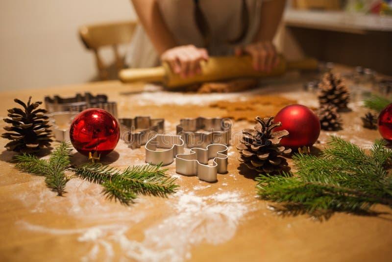 Les mains de l'enfant faisant les biscuits traditionnels de Noël dans la cuisine à la maison photo stock