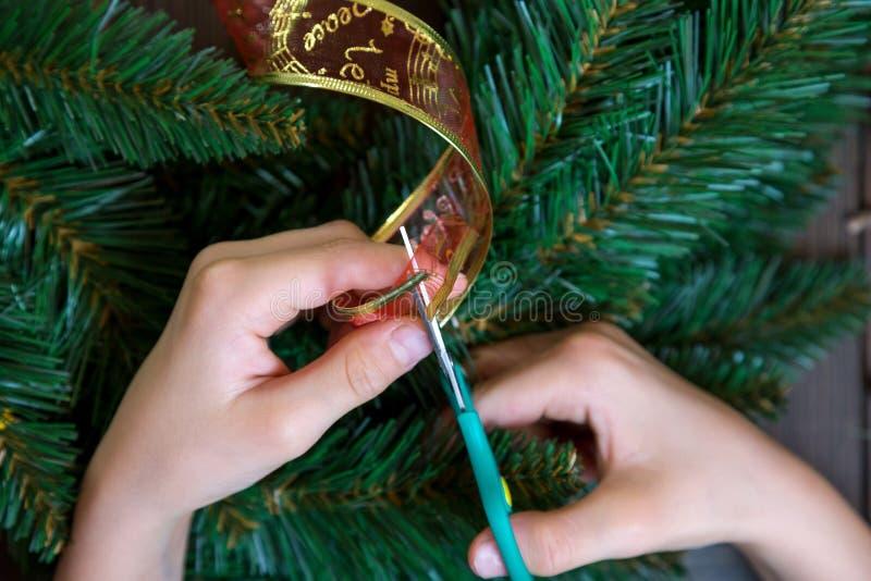 Les mains de l'enfant ont coupé le ruban rouge pour la décoration de la guirlande sur le fond en bois photo stock