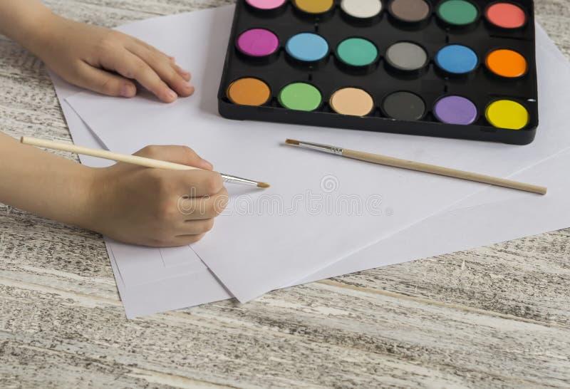 Les mains de l'enfant tenant une brosse, une peinture et un papier sur une table en bois légère images libres de droits