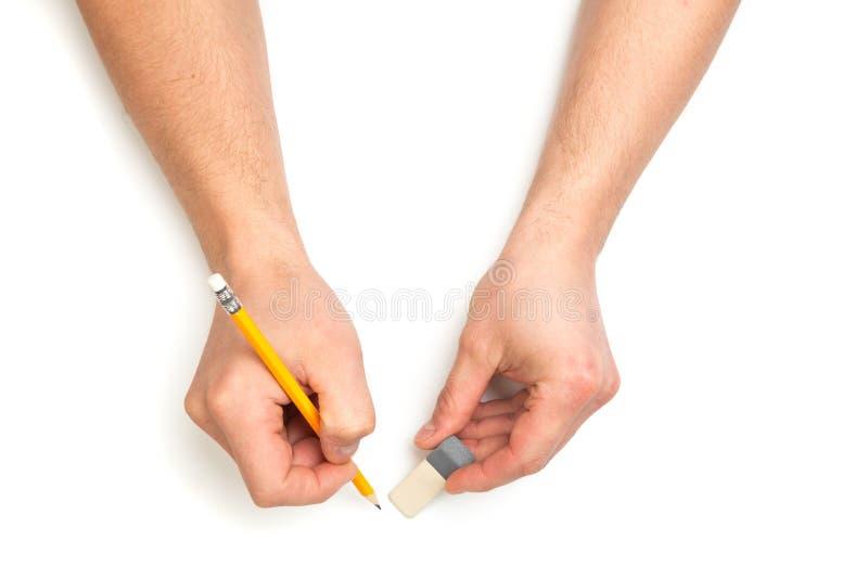 Les mains de l'homme écrivant avec le crayon et l'eracer en bois sur le fond blanc d'isolement avec l'endroit des textes photo libre de droits