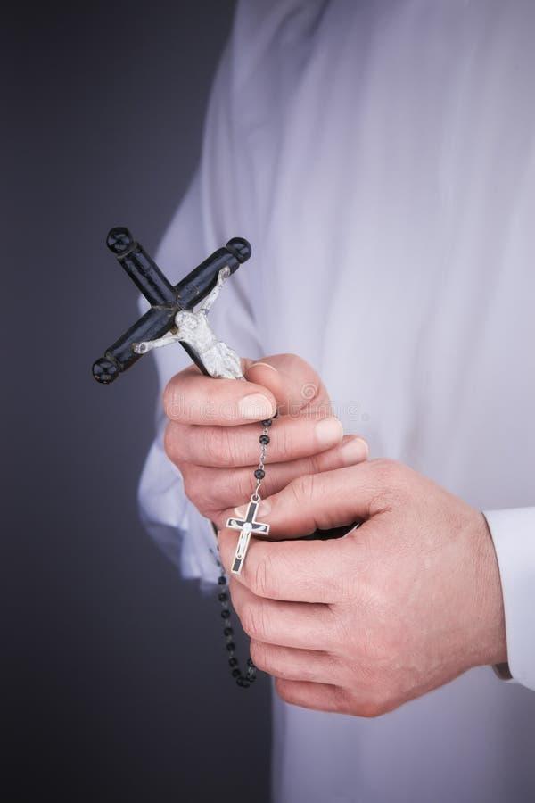 Les mains de l'homme avec un cap blanc, le crucifix et un chapelet noir images stock