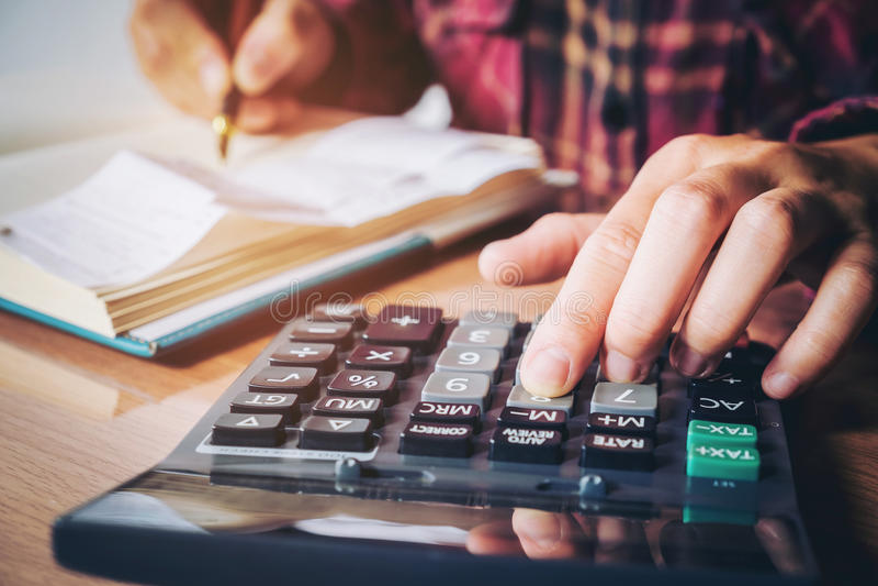 Les mains de l'homme d'affaires avec la calculatrice et le coût au bureau et au F photos stock