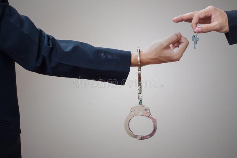Les mains de l'homme dans les menottes et la clé image stock