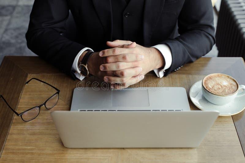 Les mains de l'homme sur la table avec l'ordinateur portable, le téléphone, le café et les verres photo stock