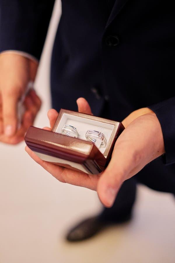 Les mains de l'homme tenant un boîtier blanc avec anneaux les épousant image stock