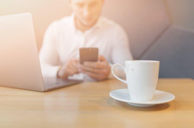 Les mains de l'homme utilisant le téléphone et l'ordinateur portable intelligents dans l'intérieur images stock