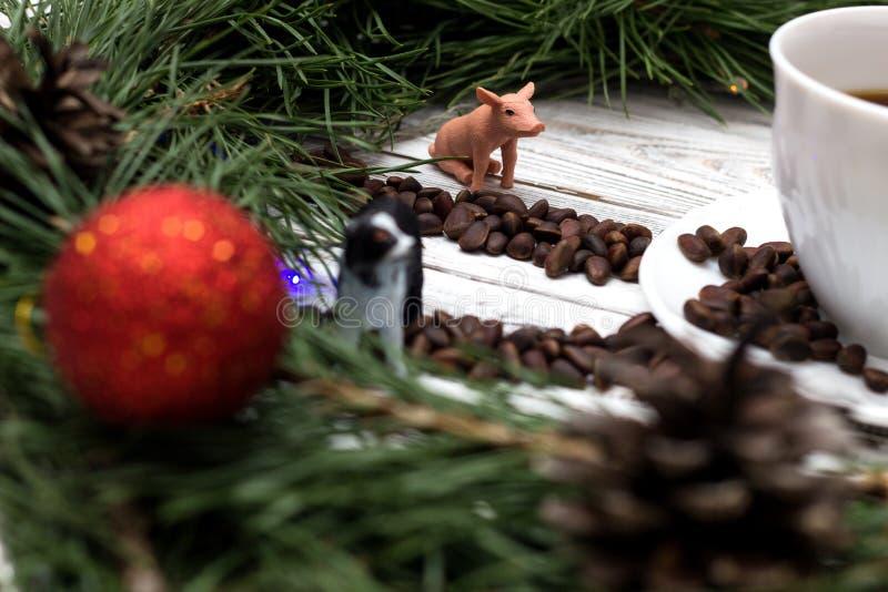 Les mains de l'horloge sont présentées des pignons, le porc de jouet et le chien, l'année sortante et nouvelle, fond en bois blan photos stock