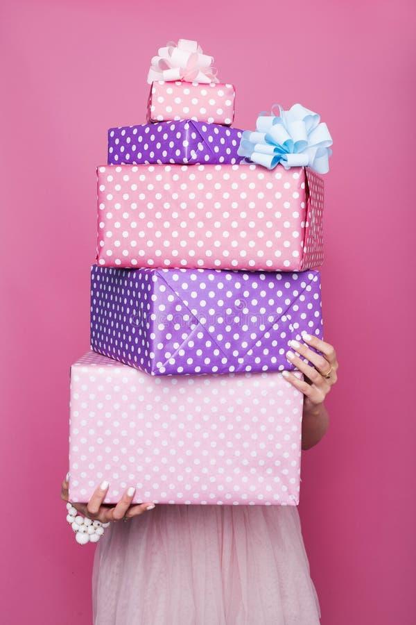 Les mains de la belle femme tenant de grands et petits boîte-cadeau colorés avec le ruban Couleurs douces Noël, anniversaire, Sai photo libre de droits