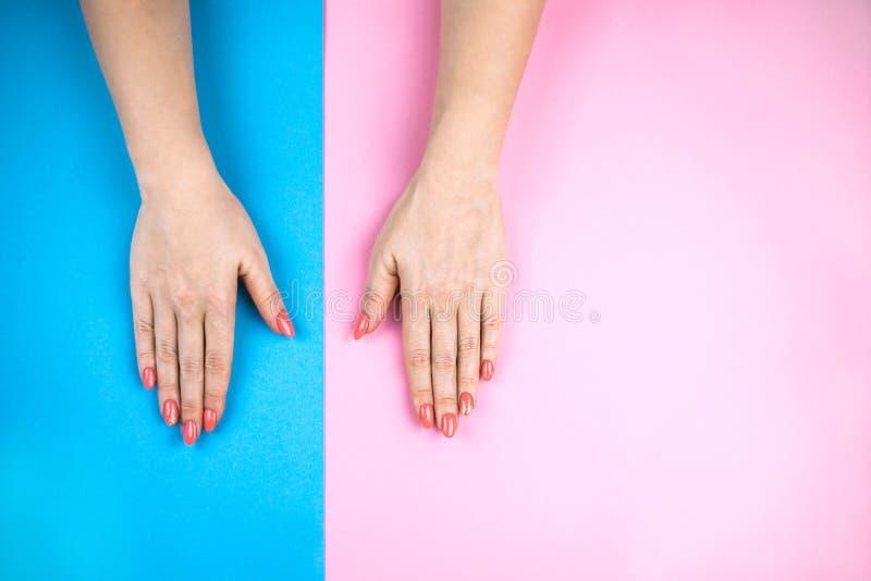 Les mains de la belle jeune femme sur le fond coloré images stock