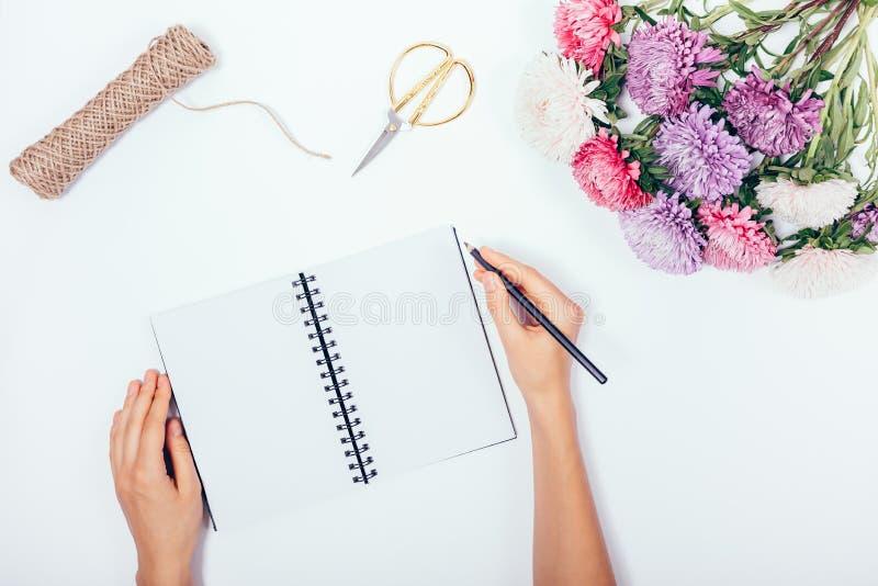 Les mains de la femelle écrivant en bloc-notes vide parmi les vacances étendues plates b photographie stock libre de droits